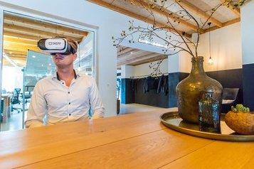 Usuario con gafas de realidad virtual en un recorrido por una oficina virtual de forma remota con SKEPP